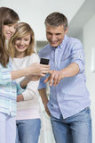 Father and daughters using smart phone at home Royalty Free Stock Photos