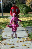 Father and Daughters Walking. Father taking his daughters out on a sunny autumn day Stock Image