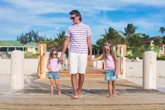 Father and daughters walking on wooden dock during Royalty Free Stock Images
