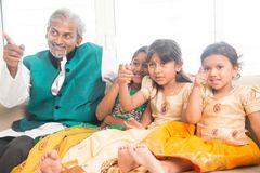 Father and daughters watching tv. Portrait of Indian family watching movie at home, all finger pointing away. Happy Asian father and children indoors lifestyle Stock Photos