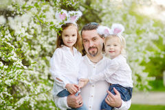 Father and daughters wearing bunny ears on Easter. Young father and his two daughters wearing bunny ears in a spring garden on Easter day Royalty Free Stock Image