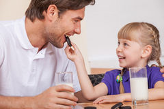 Father and daughther. Young daughter is feeding her father with chocolate cookies Stock Photos