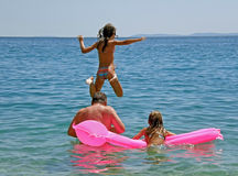 Father and daugters jumping in sea Royalty Free Stock Images