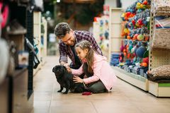 Father and dauther plays with puppy in pet shop Royalty Free Stock Photos