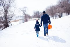 Father with daygther walking in snow, back view royalty free stock photography