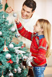 Father decorating christmas tree with daughter Stock Photography