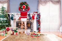 Father decorating the living room for Christmas. In his underpants and Santa outfit hanging a wreath above the mantelpiece alongside colorful gifts and a Royalty Free Stock Photo