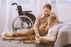 Father with disability and son playing chess. On a floor stock photo