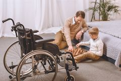 Father with disability and son playing chess on a floor with wheelchair. On foreground stock photos