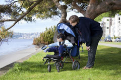 Father  with disabled son in wheelchair Stock Photos
