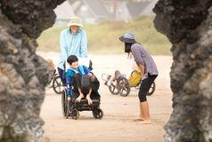 Father and disabled son in wheelchair on beach with family royalty free stock photography
