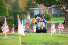 Father and disabled son in wheelchair visiting grave at cemetery. Father and disabled son in wheelchair holding flowers and visiting grave site in cemetery stock photography