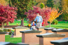 Father and disabled son in wheelchair visiting gravesite in cem. Father and disabled son in wheelchair holding flowers and visiting grave site in cemetery royalty free stock photo