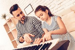 Father and Doudhter Play Piano and in Apartment. royalty free stock photo