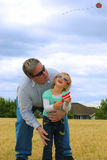 Father and doughter flying kite . Royalty Free Stock Images