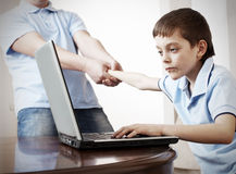 Father dragging son from the computer Royalty Free Stock Photos