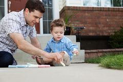 Father Drawing With Chalk on Ground Stock Photography