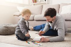 Father drawing with his little son. Father drawing with his little cute son. Man developing his child, spending free time together at home, copy space Stock Image