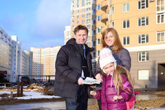 Father with drawings of apartments, daughter and realtor. Father with drawings of apartments, little daughter and realtor stand near multi-storey building at stock photography