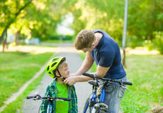 Father dresses his son bicycle helmet Stock Photography