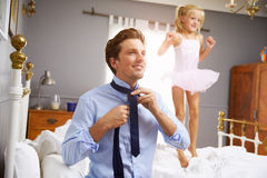 Father Dresses For Work As Daughter Plays In Bedroom Stock Images