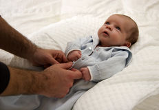 Father Dressing His Baby. Baby Gazing up to His Father Father Dressing His Baby royalty free stock photo