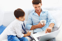 Father drinking coffee and teaching son how to use notebook. Stock Image