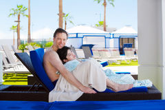Father drying off on blue lounger with disabled son off side of Stock Photo