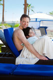 Father drying off on blue lounger with disabled son off side of Stock Image