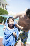 Father drying off his daughter with a towel by the pool Stock Images