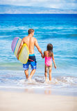 Father and Duagher on the Beach Going Surfing Stock Photography