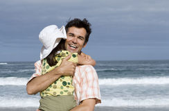 Father embracing daughter (6-8) on beach, smiling, sea in background Royalty Free Stock Image