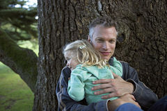 Father embracing daughter (3-5) beside tree in garden, smiling Stock Image