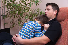 Father embracing his child. Boy, sitting on sofa at home Royalty Free Stock Images