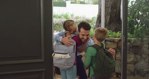 Father embracing his children at door in a comfortable home 4k. Front view of Caucasian father embracing his children at door in a comfortable home. They are stock video footage