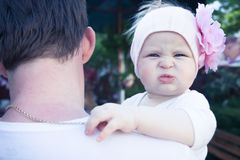 Father embracing his cute little baby. Father is looking away, baby with funny face is looking on camera stock photos