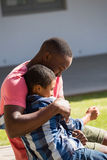 Father embracing his son in the backyard. On a sunny day Royalty Free Stock Photo