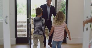Father embracing his two children as he enters the house 4k. Front view of Caucasian father embracing his two children as he enters the house. They are smiling stock video