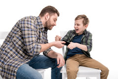 Father and emotional little son quarreling about smartphone Stock Photos