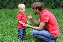 Father emotionally talks with a frustrated child. Upset toddler and his dad. Parenting difficulties concept. Family look clothing. Copy space royalty free stock photography