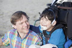 Father enjoying  beach with disabled son Royalty Free Stock Photography