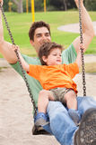 Father enjoying swing ride with his son Royalty Free Stock Photography