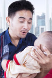Father entertain his baby in the apartment. Portrait of happy father holding and entertain male baby while sitting near the window in the apartment stock images