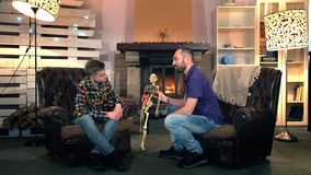 Father explaining his elder son the bone structure of human body showing on skeleton. They sitting on comfortable armchairs near the fireplace stock video