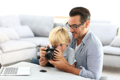 Father explaining his son how to use camera. Man with little boy playing with reflex camera Stock Images
