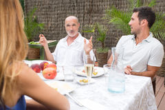 Father explaining things while talking in garden. Happy family talking while having food on terrace Stock Images