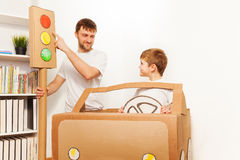 Father explaining traffic regulations to his kid. Dad explaining traffic regulations to his son, pointing to the red light signal, as they playing drivers with Stock Images