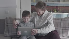 Smiling happy father and kid using digital tablet sitting on the couch in large living room. Daddy teaches his son