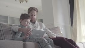 Father and kid using digital tablet sitting on the couch in large living room. Daddy teaches his kid. Happy dad and