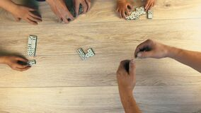 The father teaches his children to play dominoes. Flet lei. Shooting from above.